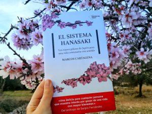 """Portada junto a flores de almendro del libro """"El sistema Hanasaki"""", de Marcos Cartagena, editado por Plataforma Editorial"""